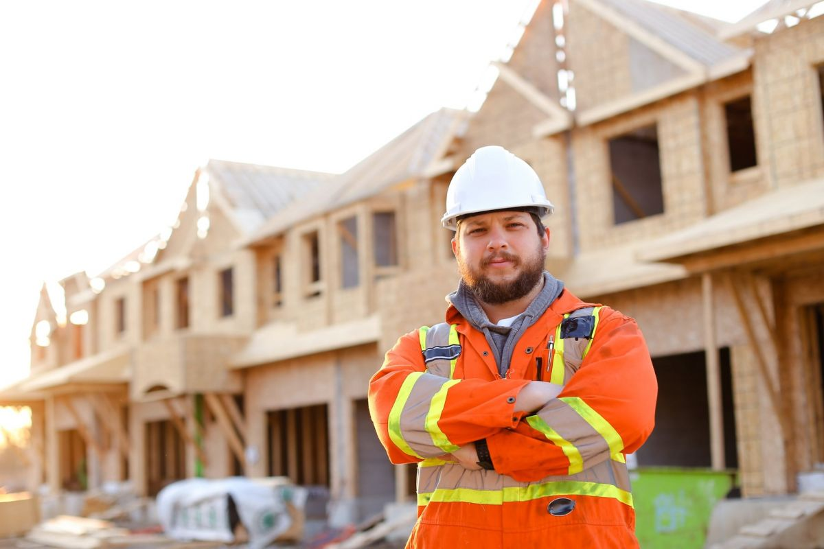 male construction worker stands in front of row of unfinished homes
