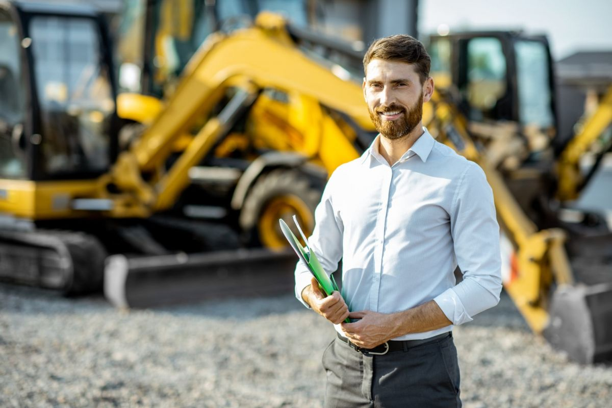 male worker standing in front of heavy equipment